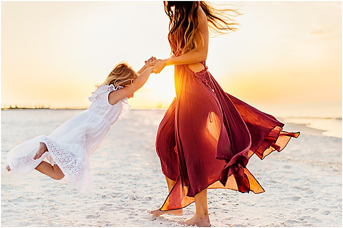Photo of a woman playing with a little girl on the beach