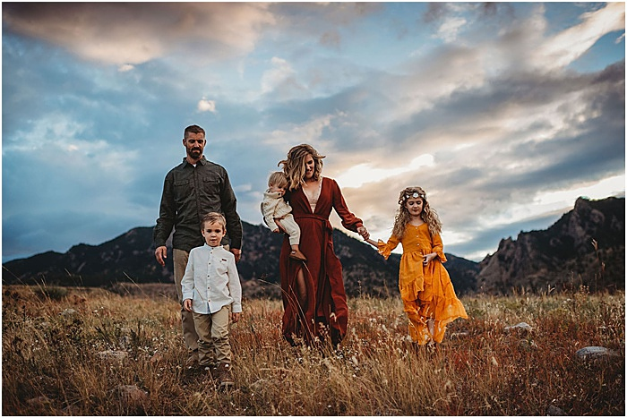Photo of a family walking on a field with mountains in the background