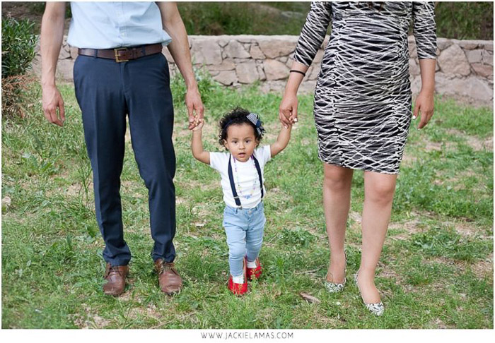 sweet family portrait of parents holding a little girls hand outdoors