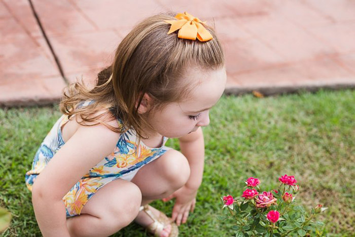 lifestyle portrait of a little girl crouching on the grass