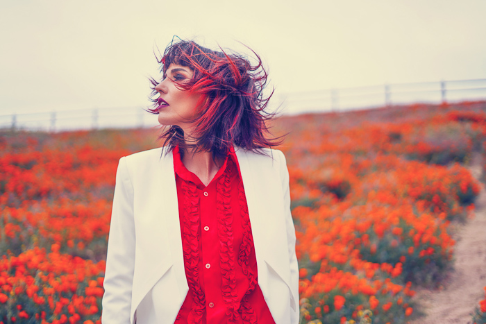 Portrait photo of a girl with orange flowers in the background