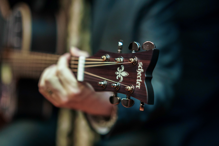Close-up photo of the hands of a man holding a guitar