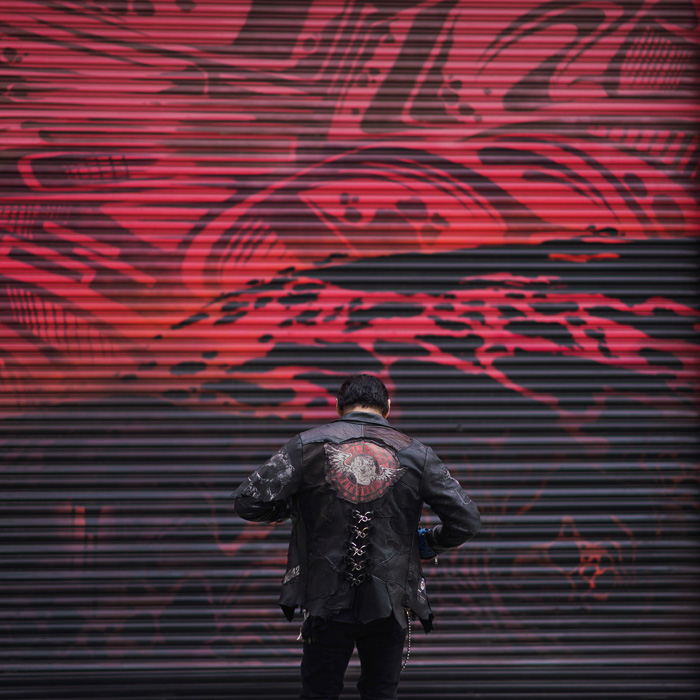 Photo of a man in a leather jacket in front of an abstract background