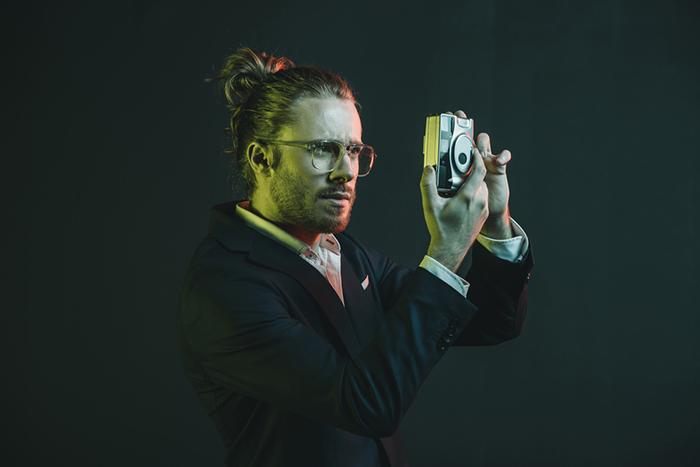 एक आदमी कैमरा पकड़े हुए है और एक गहरे रंग की पृष्ठभूमि के सामने लेंस को देख रहा है