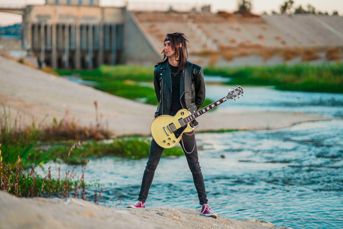A guitarist standing in front of a river