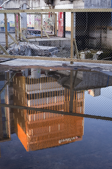 Photo of a tall building reflecting in a puddle on the street