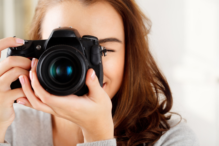 Close-up photo of a woman taking a photo with a dslr camera