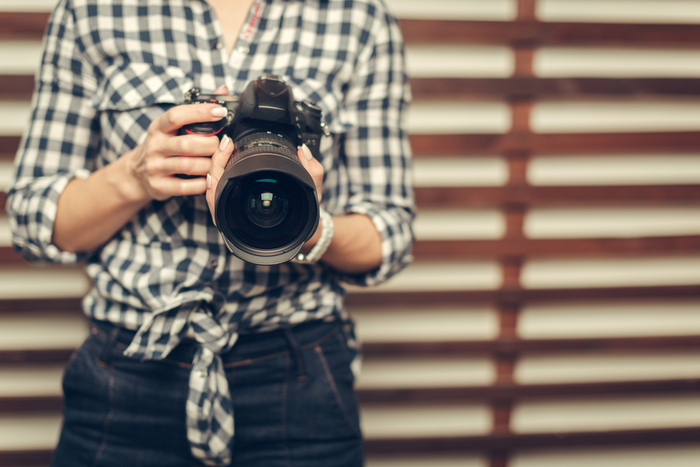 Photo of a woman holding a dslr camera in her hand