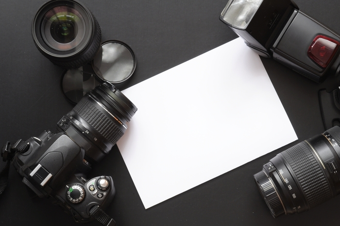 Photo of a camera, lenses, and a white sheet of paper