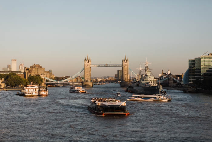 Photo of ships on the Thames river with the London Bridge in the background