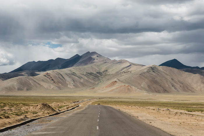 Photo of a road with mountains in the background leading lines