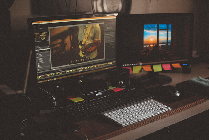 Two monitors on a desk, one of the screens shows an image being edited
