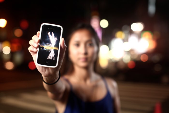 A woman holding a smartphone, the phone is in focus, while the rest of the image is blurred