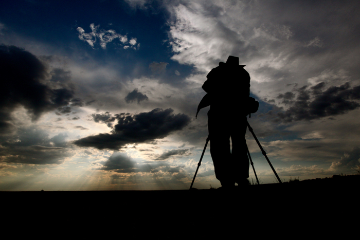 A silhouette of a photographer with a tripod
