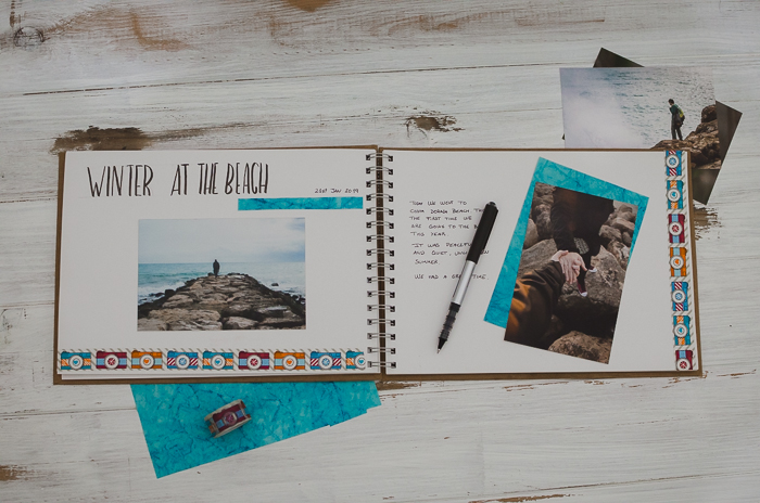 overhead view of a notebook, photos and stationary for making a photo journal