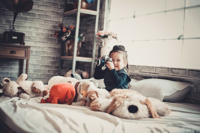 Photo of a little girl sitting on a bed taking photos