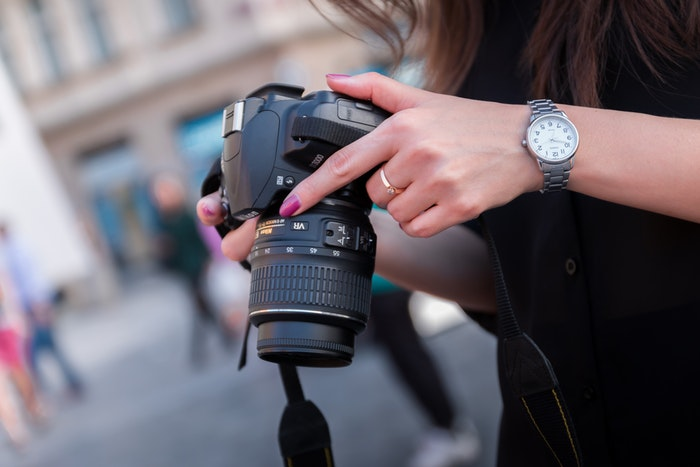 Photo of a woman holding a dslr camera
