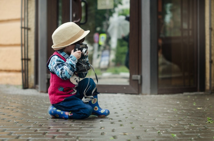 Photo of a little girl taking a photo on the street