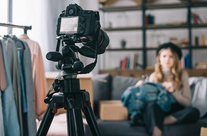 A camera on a tripod recording a vlogger