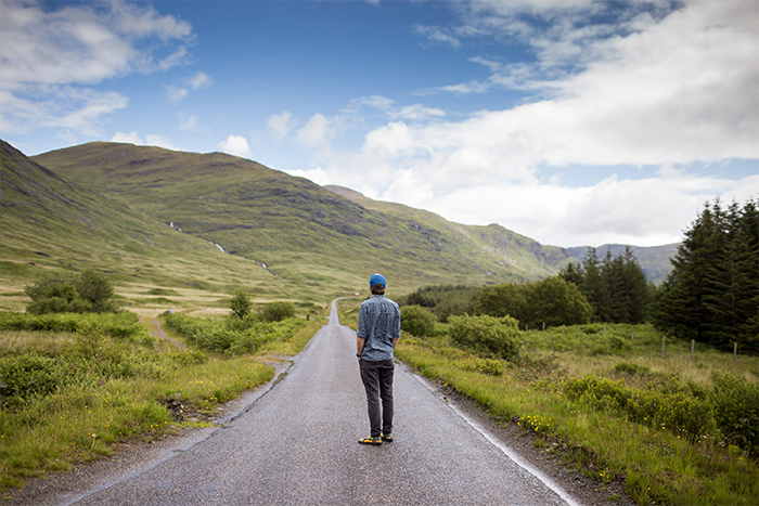 A landscape image with a man standing in the middle of a countryside road.