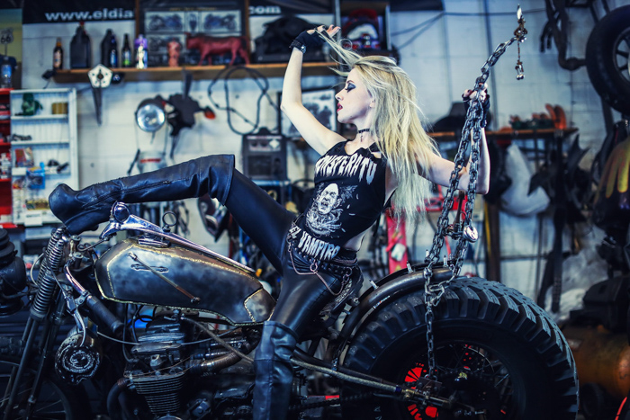 a girl in biker gear posing on a motorbike