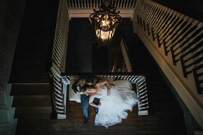 an overhead portrait of a newlywed couple posing on a staircase