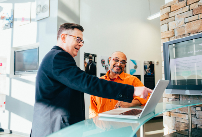 two men choosing photos to print at a printing company