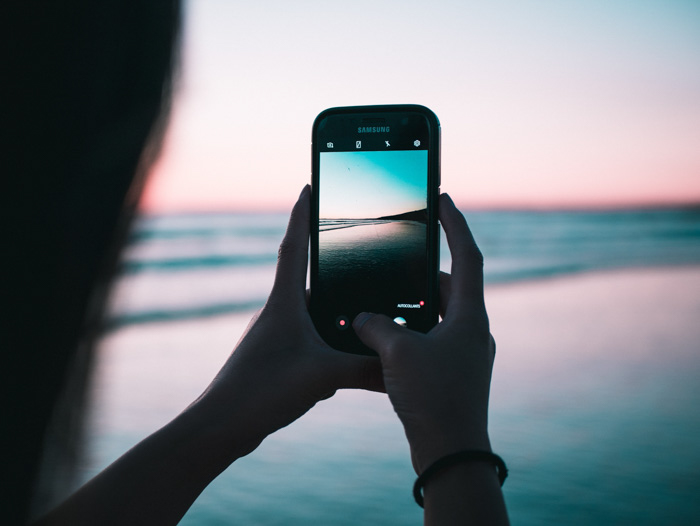 a girl taking a beach photo on a smartphone at sunset