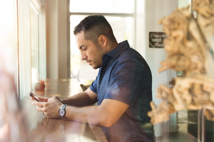 a man using his smartphone at a wooden counter
