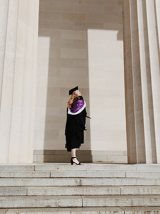 a student in graduation clothes posing on steps