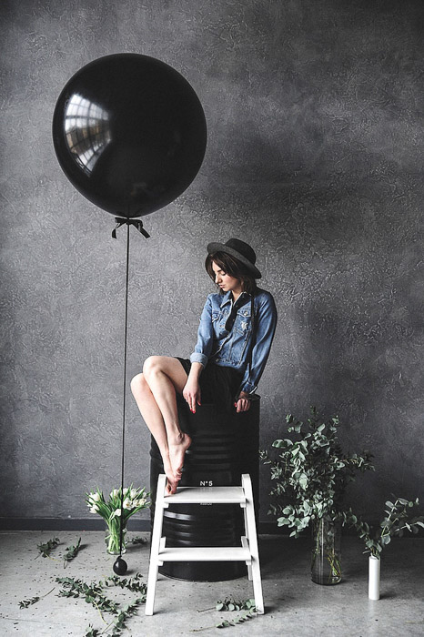 portrait of a stylish female model sitting by a black balloon