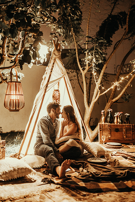 A couple sitting in an indoor teepee