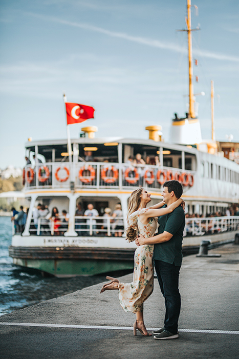 A couple embracing at a pier in front of a large boat
