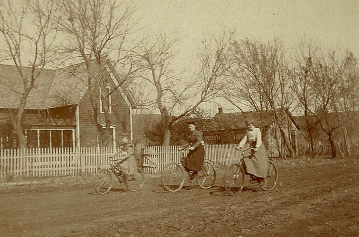 Old photo of a family cycling in the countryside