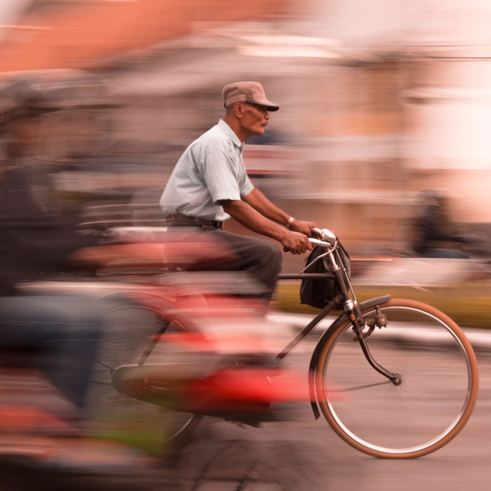 Photo of an older man cycling with motion blur effect