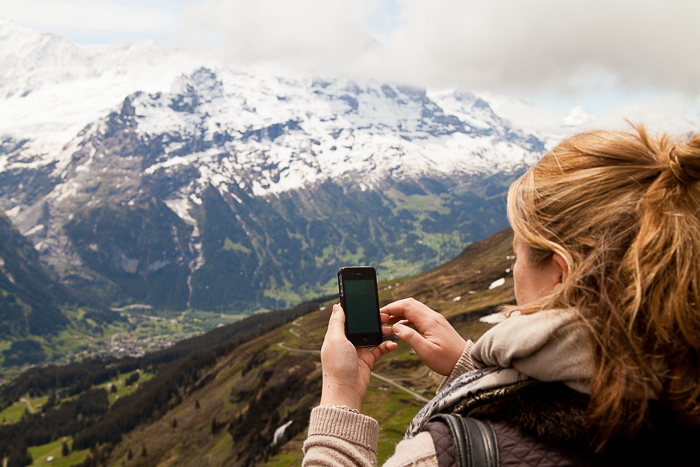 a girl shooting a landscape image on a smartphone