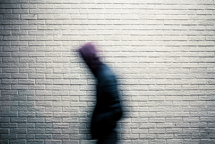 A person walking in front of a wall, captured with motion blur