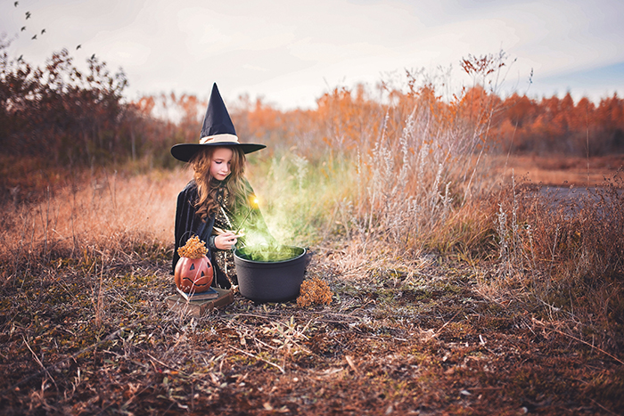 A little girl dressed as a witch. Her cauldron has been edited to look like there is a potion brewing inside it.
