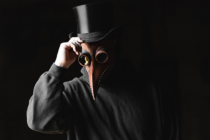 A person in a scary mask in front of a black background