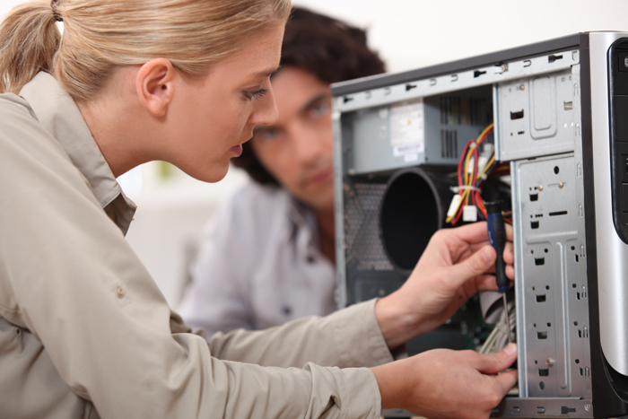 Photo of a woman checking the inside of a computer