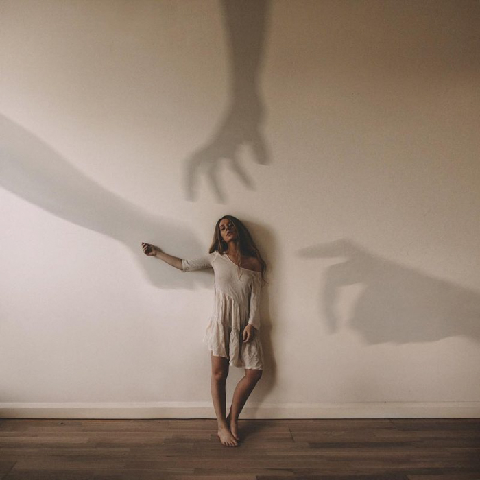 Photo of a woman with shadow hands on the wall
