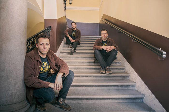 a cloned three times sitting in various positions in a courtyard