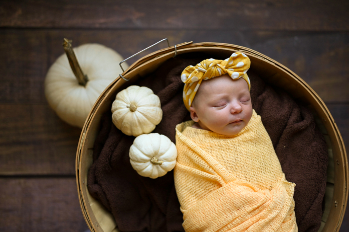 Photo of a baby sleeping with pumpkins around