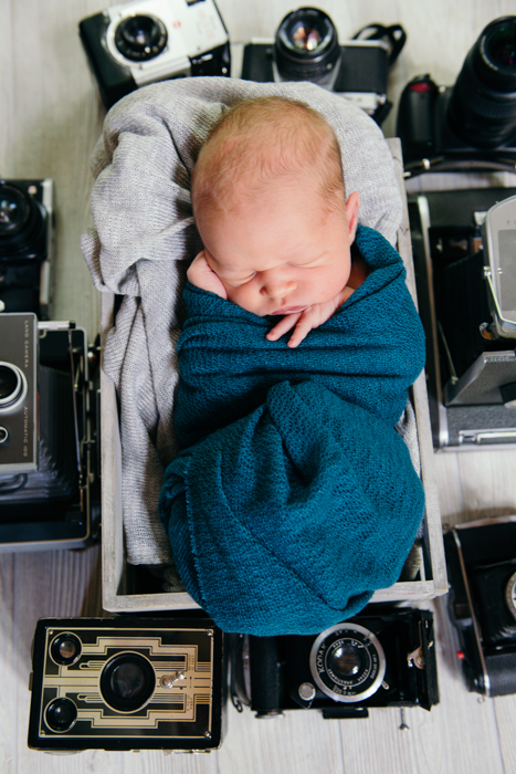 Photo of a baby sleeping with old cameras around him
