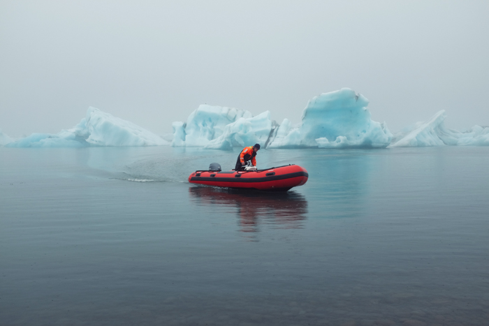 A red boat on arctic waters with a man standing inside of the boat