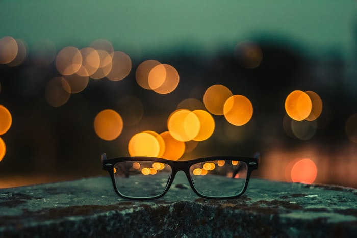 a pair of glasses on a wall, bokeh lights in the background