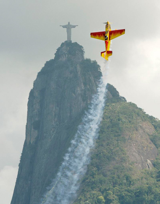 Photo of a plane flying in the same posture as the Jesus statue in the background