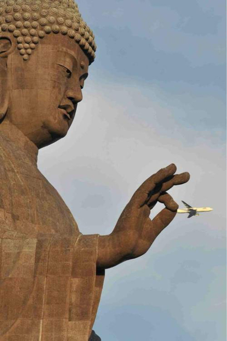 Photo of a Buddha statue looking like it is holding a plane