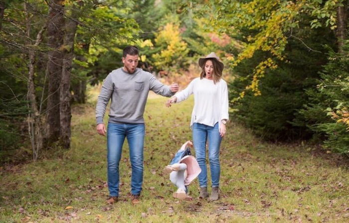 Photo of a couple dropping their little kid on the ground