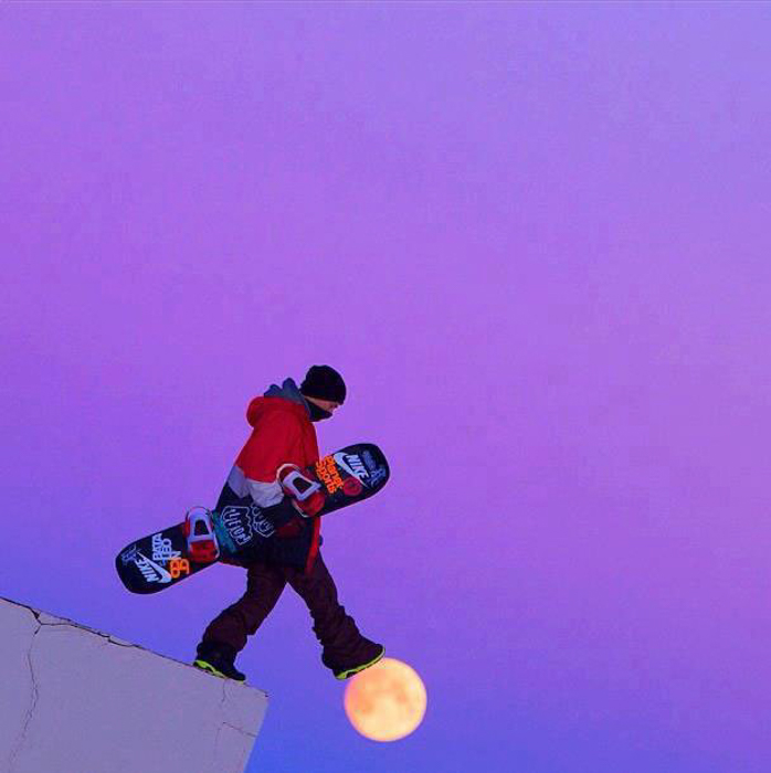 Photo of a snowboarder looking like he is stepping on the moon